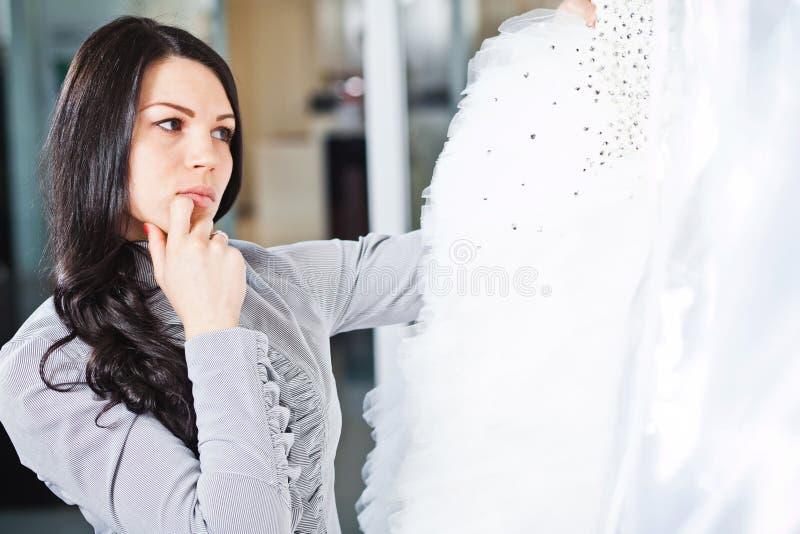 Den härliga flickan väljer hennes bröllopsklänning Stående i brud- sa royaltyfria foton