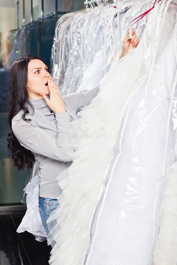 Den härliga flickan väljer hennes bröllopsklänning Stående i brud- sa royaltyfri foto
