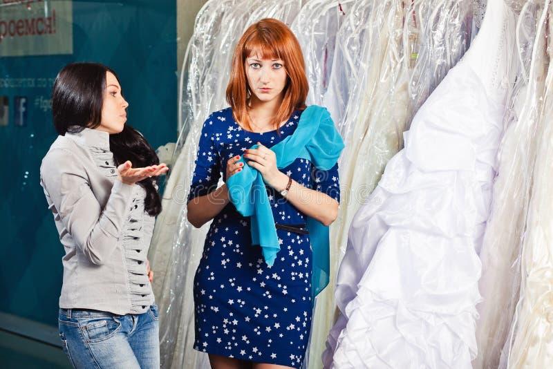 Den härliga flickan väljer hennes bröllopsklänning Stående i brud- sa arkivfoto