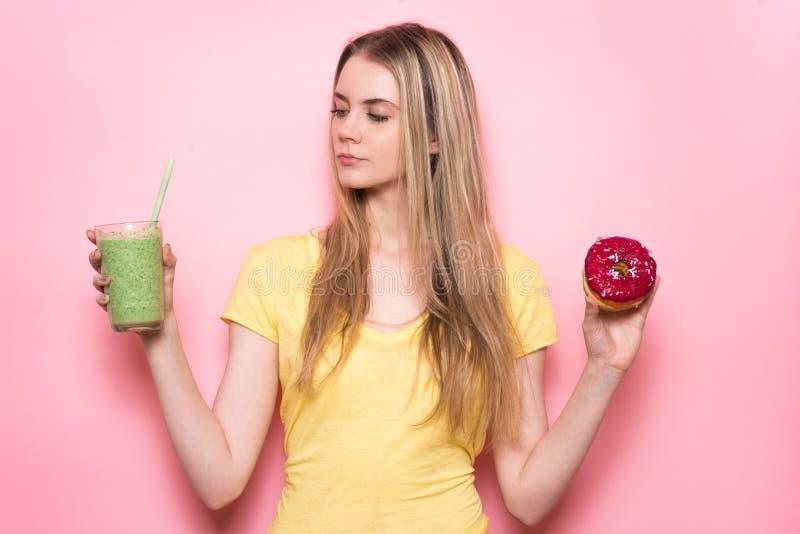 Den härliga flickan väljer mellan den sunda gröna gluten-fria organiska smoothien och sjuklig mat Primat begrepp för näring royaltyfri foto