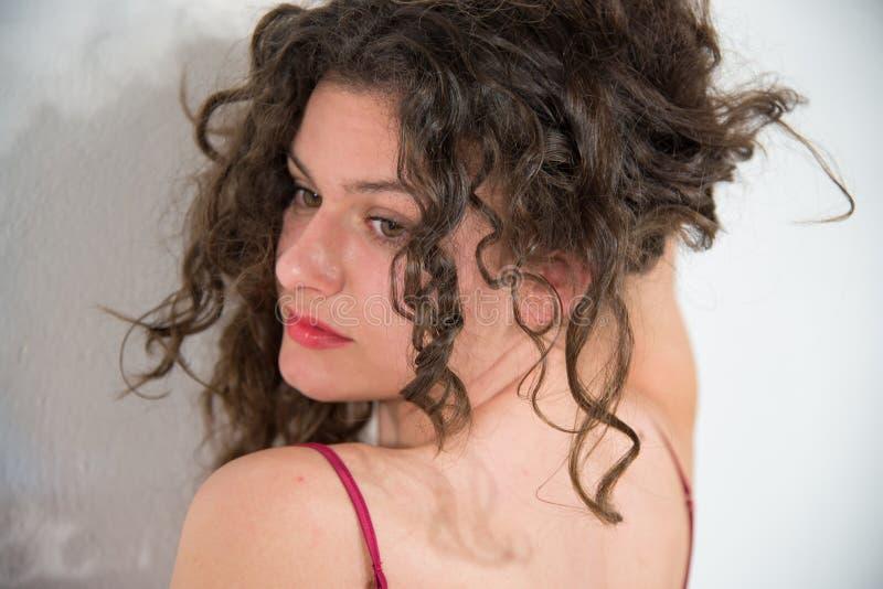 Den härliga flickaståenden med brunt hår som är rört i röd satängunderkjol, vänder tillbaka arkivbilder
