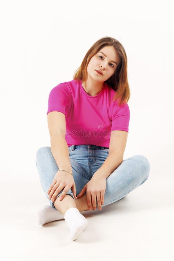 Den härliga flickatonåringen i rosa t-skjorta och jeans sitter arkivbilder