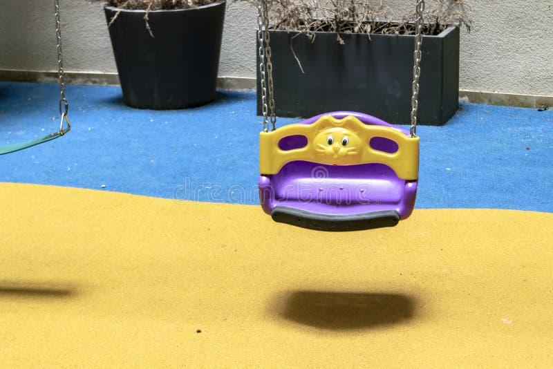 Den härliga forsen av färgrika barn svänger med guling, och blått färgar bakgrund arkivfoto