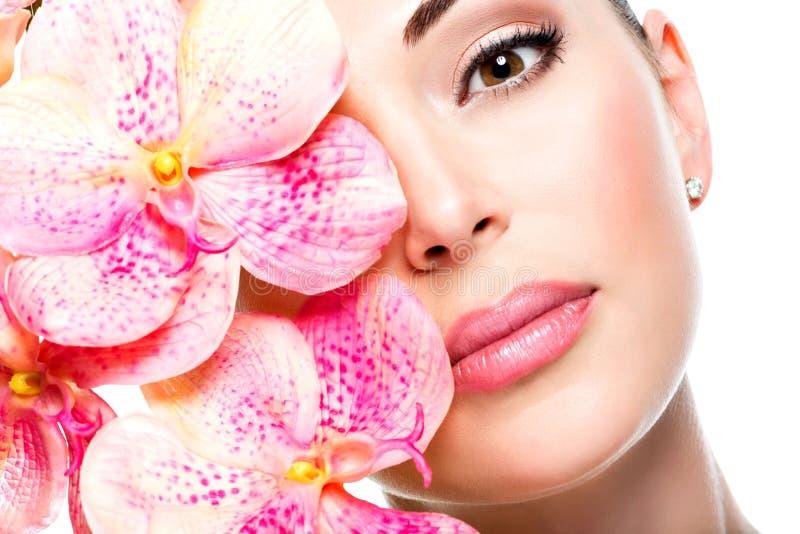 Den härliga framsidan av kvinnan med sund hud och rosa färger blommar arkivbilder