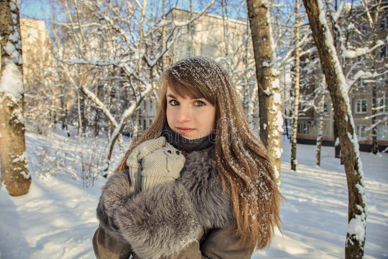 Den härliga fundersamma flickan med rött hår och snöflingor på håret är på bakgrunden av en vinterstad på en solig dag royaltyfri fotografi