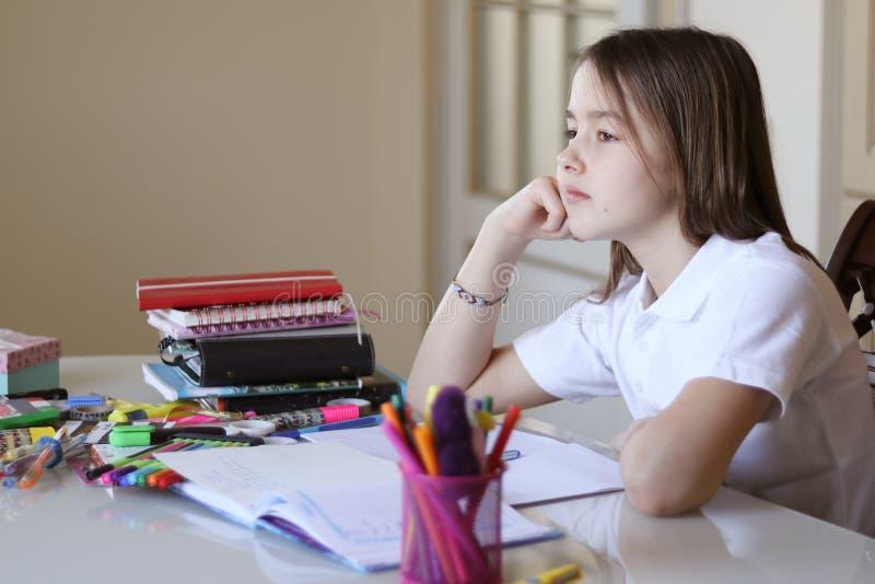Den härliga fundersamma skolflickan dagdrömmer, medan göra hennes läxa arkivbilder