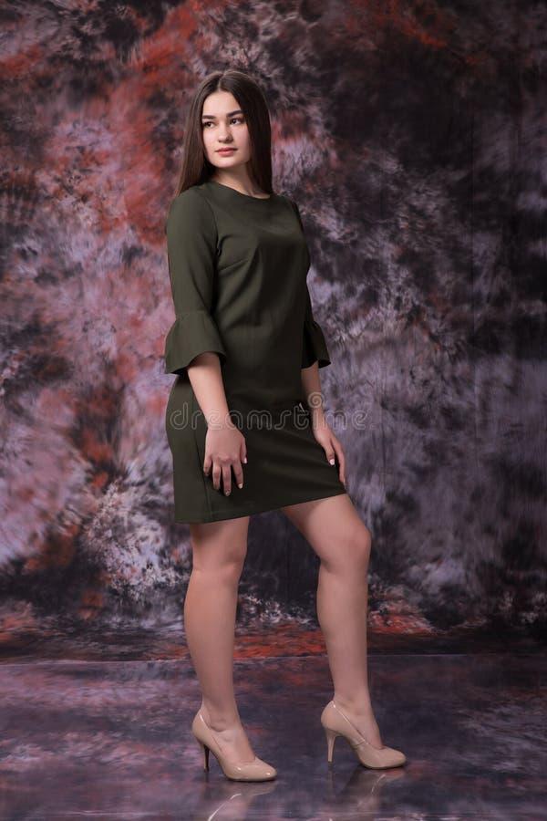 Den härliga fylliga flickan i en grön klänning som poserar över marmor, färgade bakgrund bedsheetmode lägger förföriskt vitt kvin arkivbilder