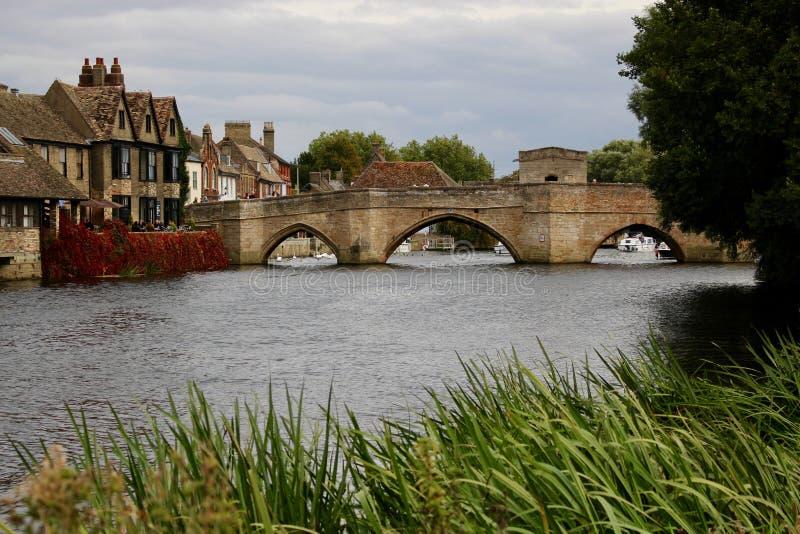 Den härliga gamla medeltida bron över den stora Ousen med det forntida brokapellet från Hemingford grå färger bevattnar ängen fotografering för bildbyråer