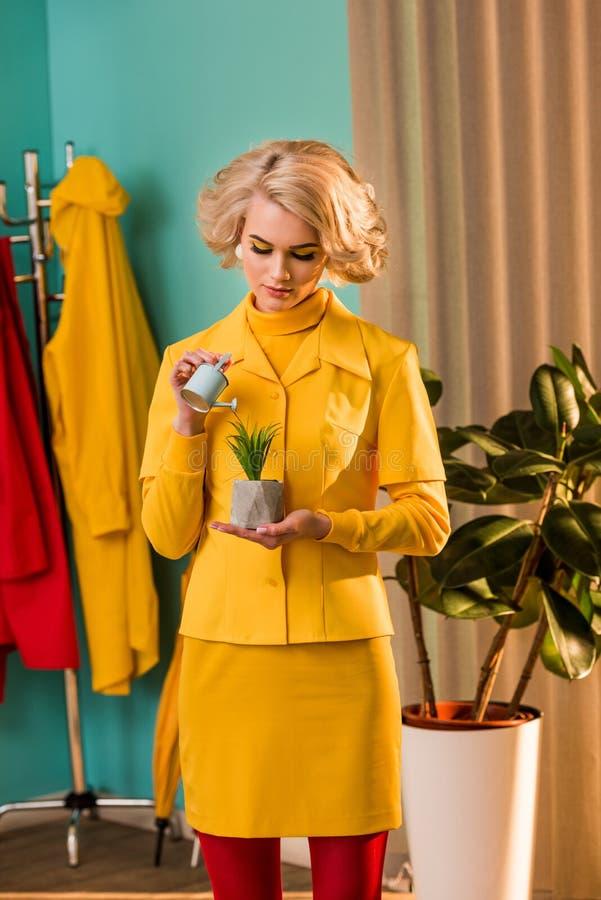 den härliga gammalmodiga kvinnan i gul klänning som bevattnar den inlagda växten med litet bevattna kan royaltyfri fotografi