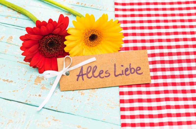 Den härliga gerberatusenskönan blommar och kortet med text, Alles Liebe, hjälpmedelförälskelse arkivfoto