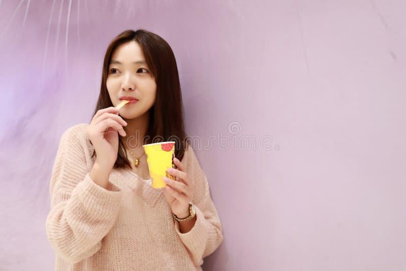 Den härliga gladlynta flickan äter glass arkivfoto