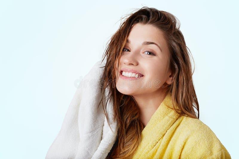 Den härliga gladlynta kvinnlign med vått mörkt hår bär badrocken, rymmer handduken och att vara glad att ta duschen och tvätta av royaltyfri bild