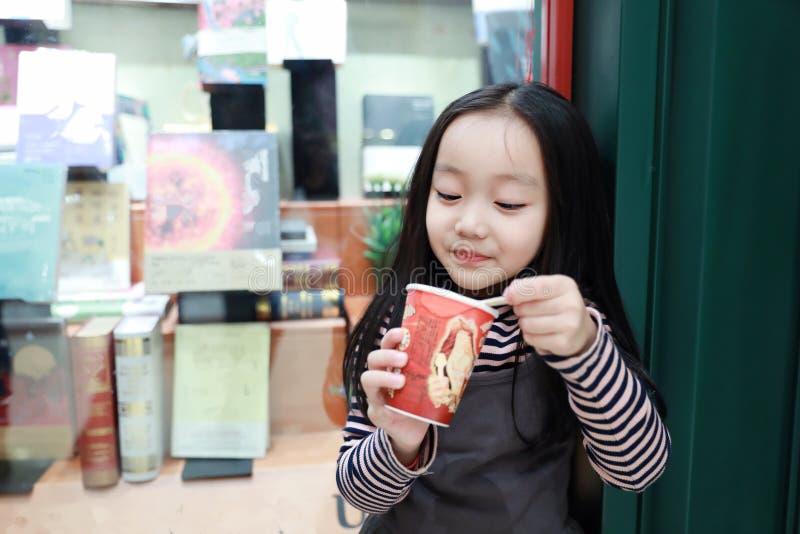 Den härliga gladlynta lilla flickan äter glass arkivfoton