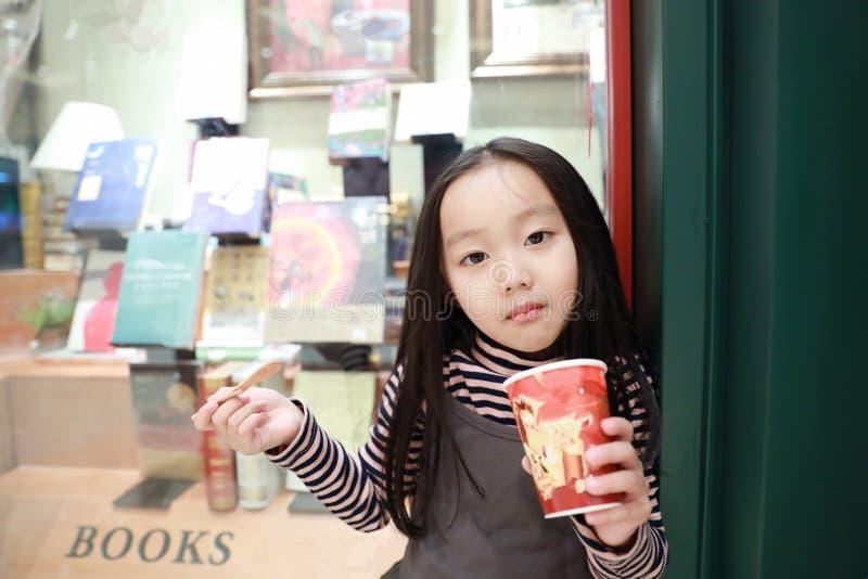 Den härliga gladlynta lilla flickan äter glass royaltyfri bild