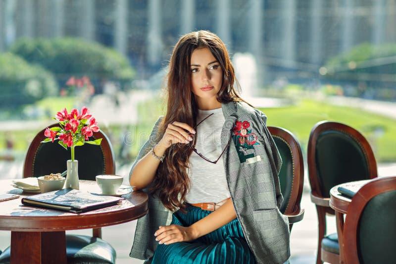 Den härliga glamorösa och stilfulla brunettflickan i exponeringsglas sitter in fotografering för bildbyråer