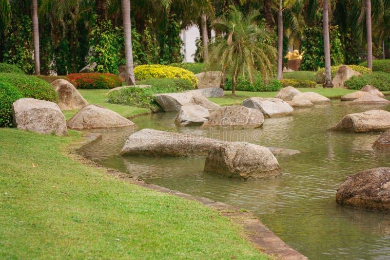 Den härliga gräsplanträdgården med vaggar och floden royaltyfri fotografi