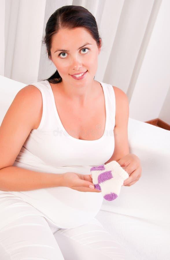 Den härliga gravid kvinnaholdingen behandla som ett barn sockor arkivfoton