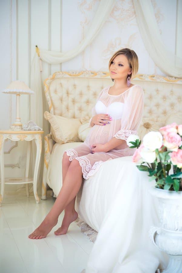 Den härliga gravida flickan i ett hem beklär sammanträde i inre på en säng av rosor royaltyfri bild