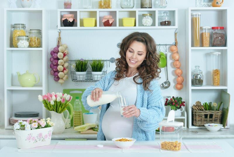 Den härliga gravida kvinnan med mjölkar arkivbilder