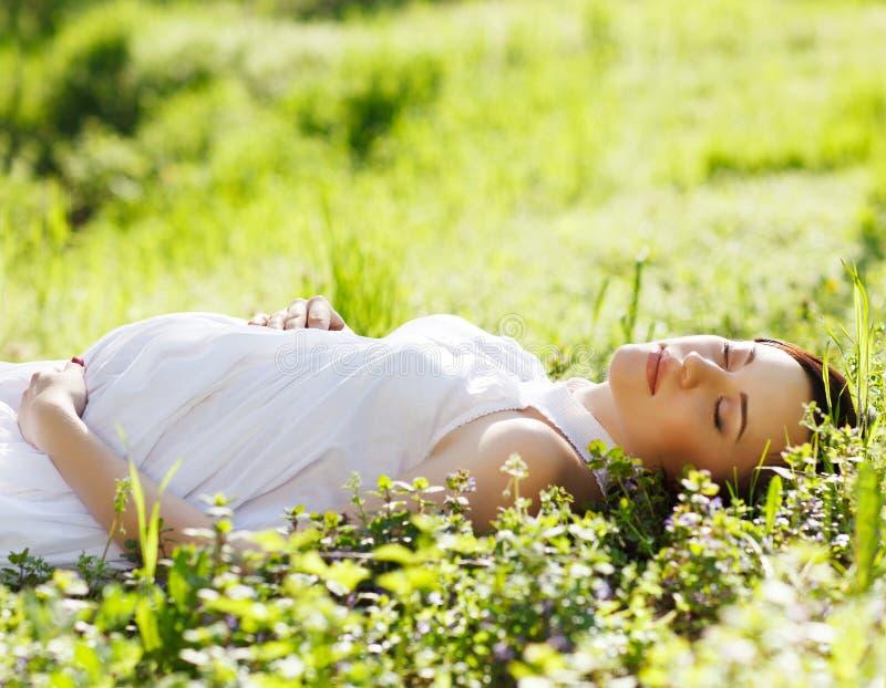 Den härliga gravida kvinnan på gräs parkerar på våren royaltyfri fotografi