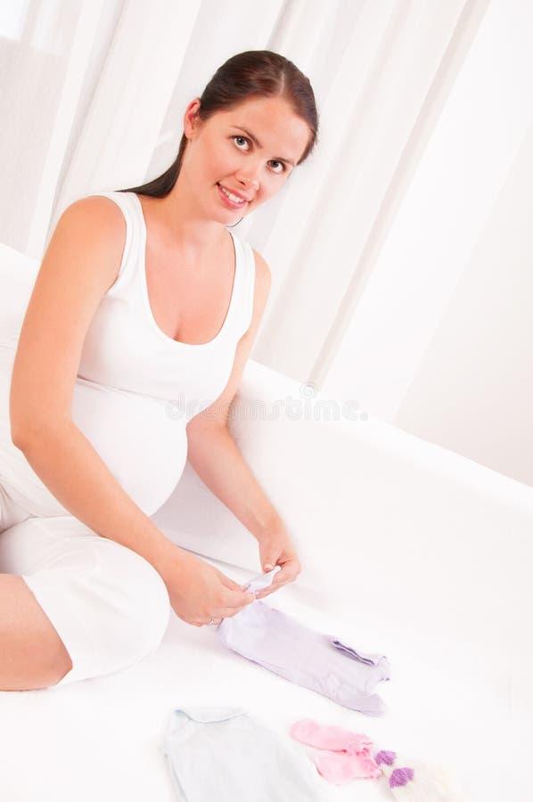 Den härliga gravida kvinnan som packar upp, behandla som ett barn kläder arkivbild