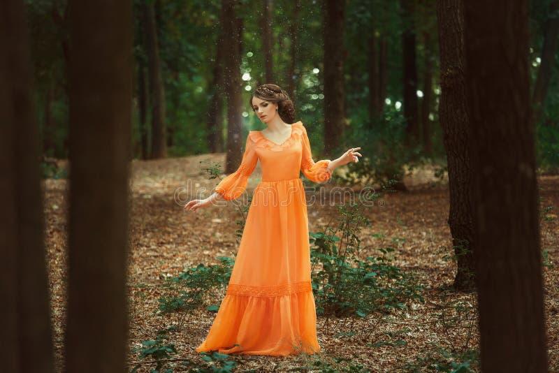 Den härliga grevinnan i en lång orange klänning royaltyfri bild