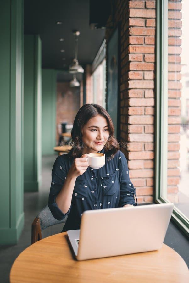 Den härliga gulliga asiatiska unga kvinnan i kafét, tycker om att dricka cof royaltyfri fotografi