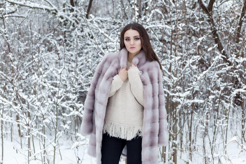 Den härliga gulliga eleganta flickan i ett pälslag går i den ljusa frostiga morgonen för vinterskogen royaltyfria bilder