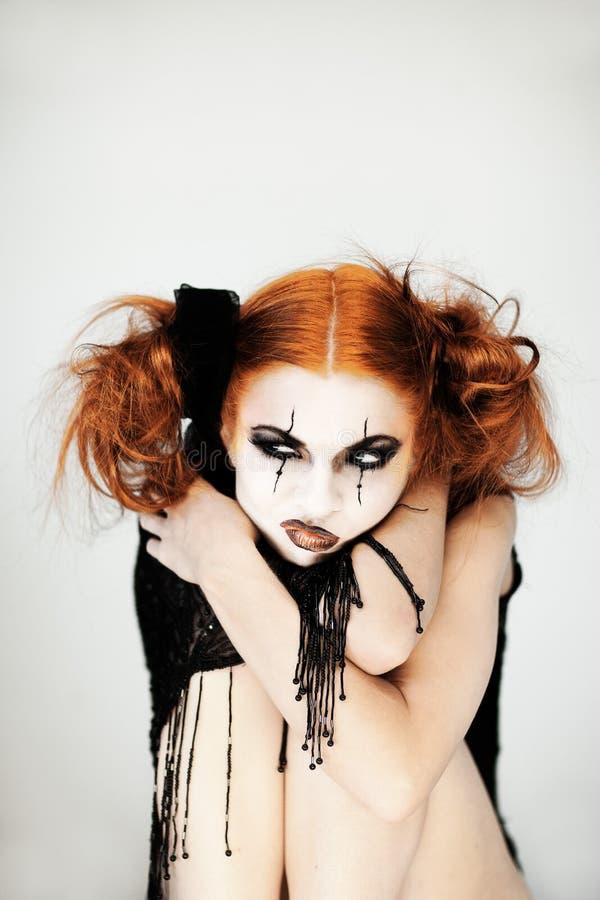 Den härliga gulliga kvinnan med halloween utgör och rött hår arkivfoton