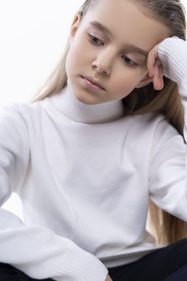 Den härliga gulliga tonåriga flickan som bär en vit halvpolokragetröja och jeans, sitter på golvet bakgrund isolerad white annons arkivfoton