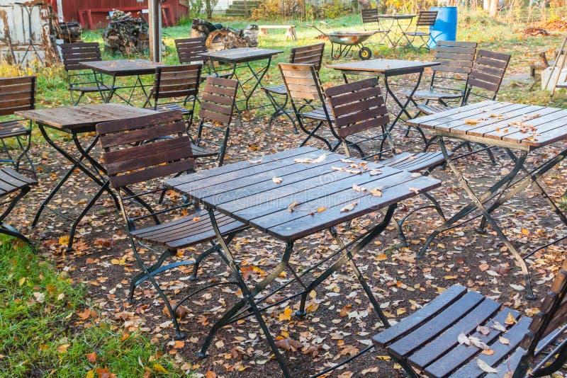Den härliga hösten i gammalt utomhus- kafé i parkerar - våta tabeller och stolar med färgrik lövverk royaltyfria bilder