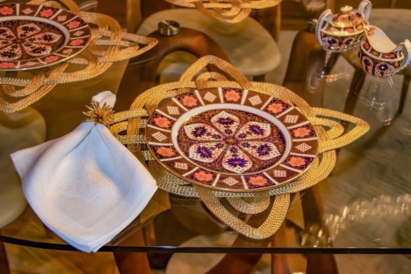 Den härliga höstställeinställningen på den glass tabellen med guld flätade ställetorkdukar och vita servetter arkivfoton
