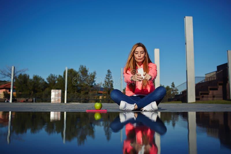 Den härliga hipsterflickan tar bilder av hennes själv med mobiltelefonen royaltyfri fotografi