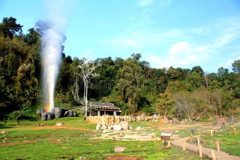 Den härliga huggtanden Hot Springs gör regnbågen med bakgrund för den gröna växten och för blå himmel på Doi Pha Hom Pok National arkivbild