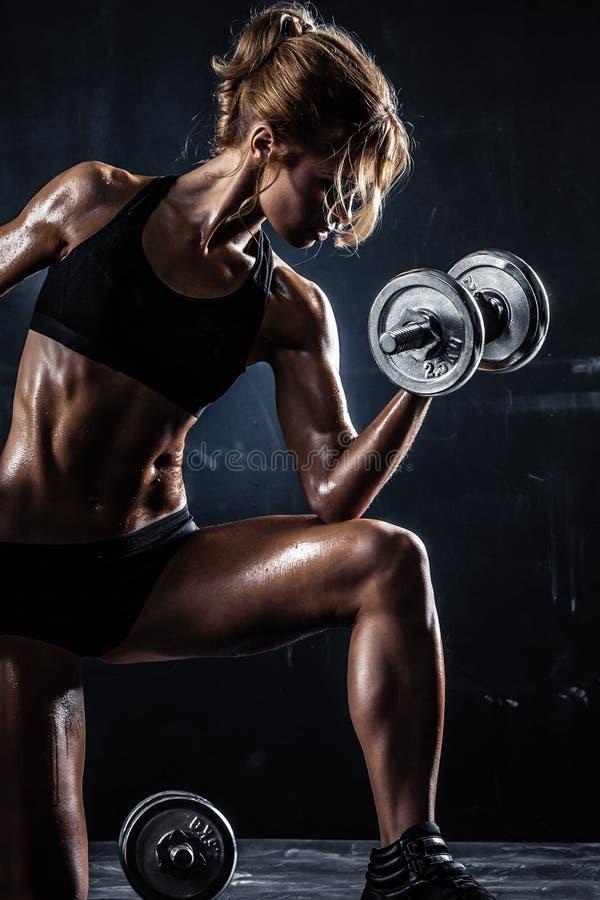 Den härliga idrotts- kvinnan gör övningar med hantlar arkivbild