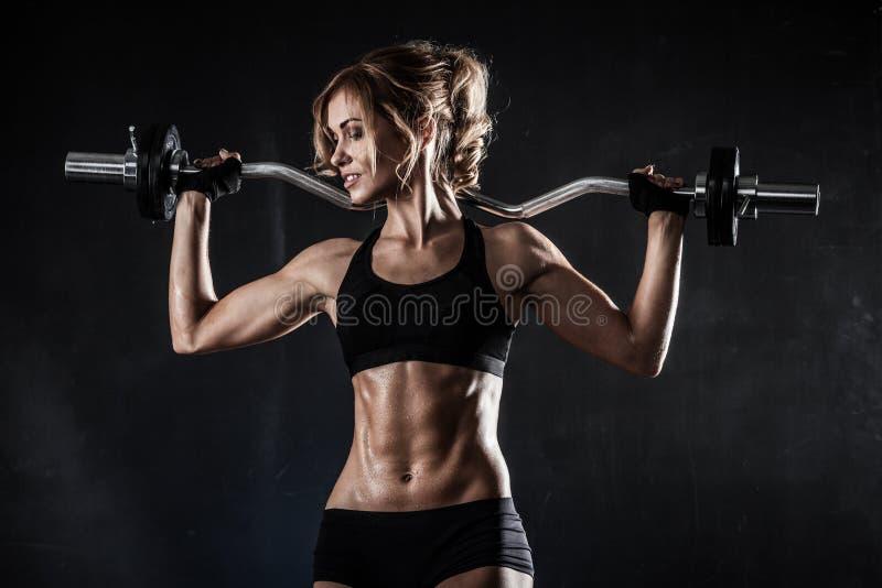 Den härliga idrotts- kvinnan gör övningar med skivstången arkivbild