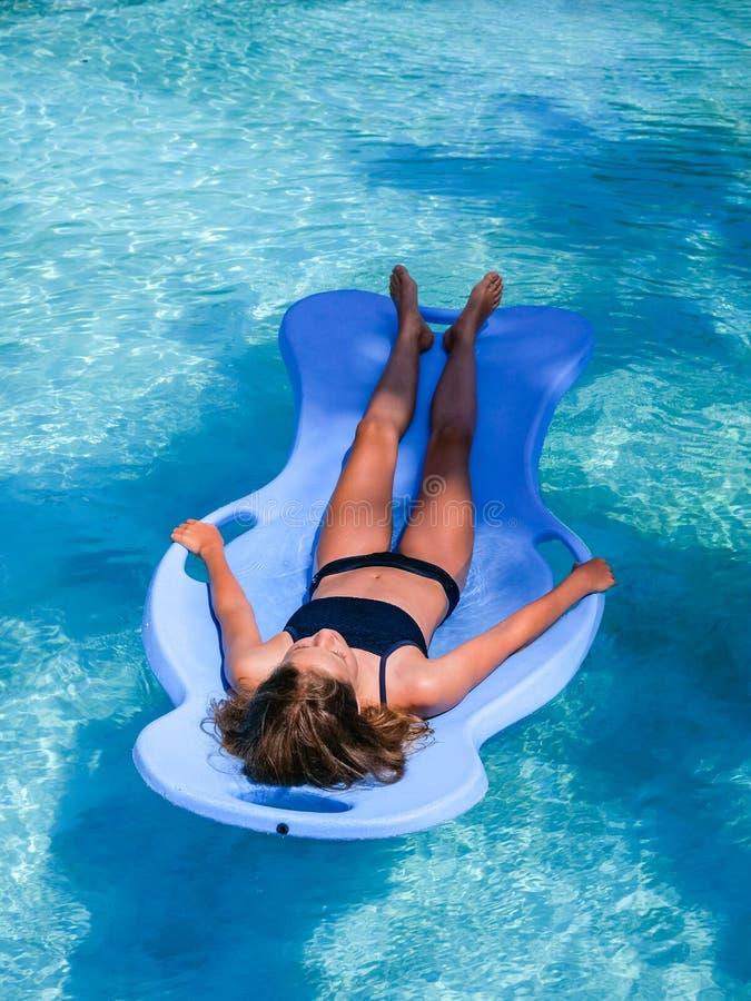 Den härliga idrotts- solen garvade flickan som svävar på en pölflöte i en simbassäng på semester royaltyfria foton