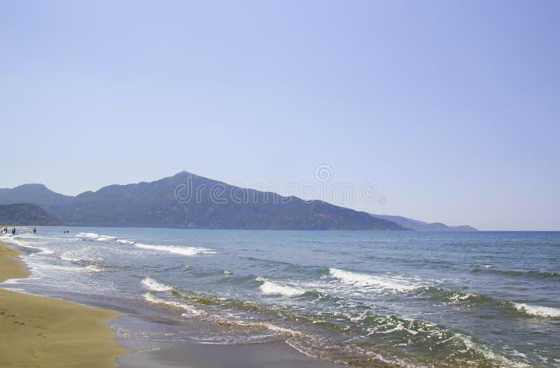 Den härliga Iztuzu stranden i Turkiet Den ljusa sommarsolen skiner över den breda sandkustlinjen Berg p? bakgrund Vinkar arkivfoto
