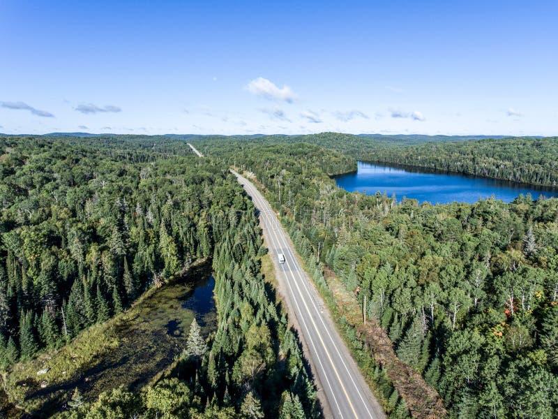 Den härliga Kanada camparebussen som kör på den ändlösa vägen, sörjer trädskogen med sjöar förtöjer bakgrund för loppet för den f royaltyfri foto