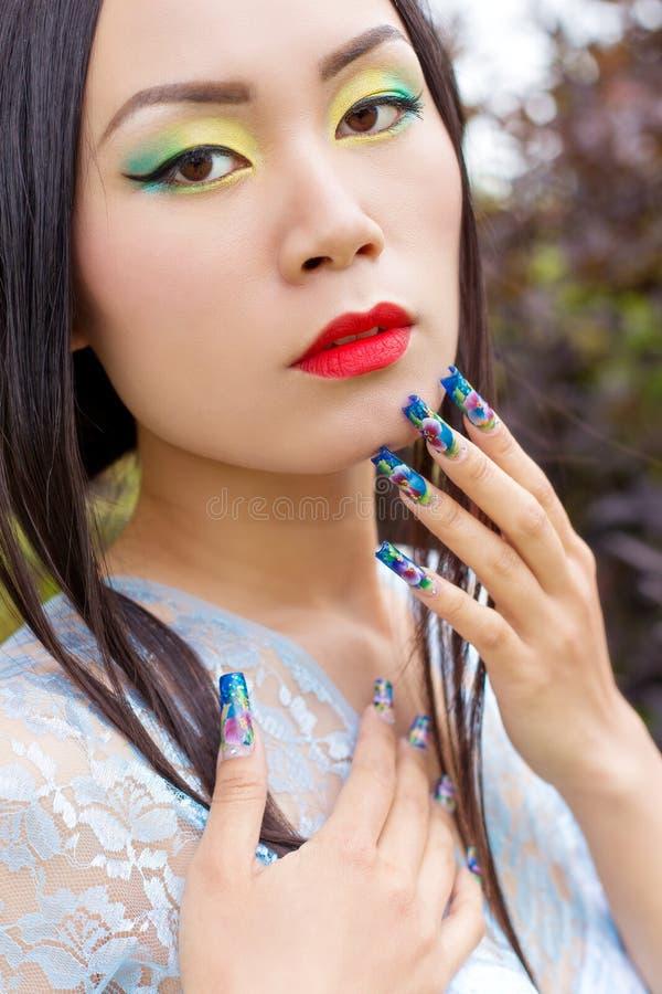 Den härliga kinesiska flickan i kimono med långt falskt spikar nära framsidan med röd läppstift royaltyfria bilder