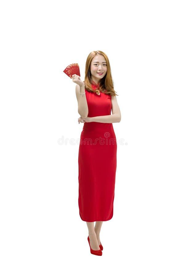 Den härliga kinesiska kvinnan i den röda traditionella klänningen som rymmer, packar in royaltyfri fotografi