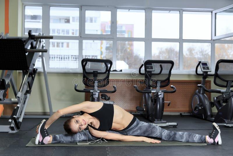 Den härliga konditionflickan som gör yoga som sträcker övning, vippar på till sidosammanträdet på golvet och att lyssna till musi arkivfoto