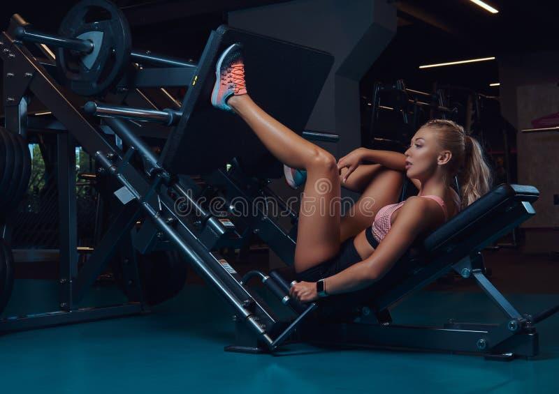 Den härliga konditionkvinnan i sportswearen som gör övning på benen, trycker på maskinen i idrottshallen royaltyfria bilder