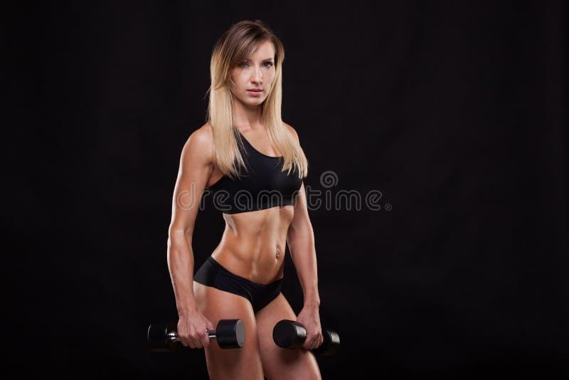 Den härliga konditionkvinnan lyfter hantlar Sportig flicka som visar hennes välutbildade kropp Isolerat på mörk bakgrund arkivbilder