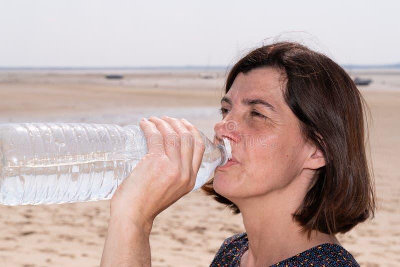 Den härliga konditionmitt åldrades brunettkvinnan som dricksvatten efter utarbetar att öva på sommar i utomhus- stående för stran royaltyfri bild