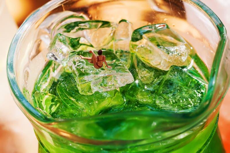 Den härliga kvinnabikinin som sunning på iskuber, gör grön lemonadkannaexponeringsglas Förnyande drinksommartidbegrepp med royaltyfria foton