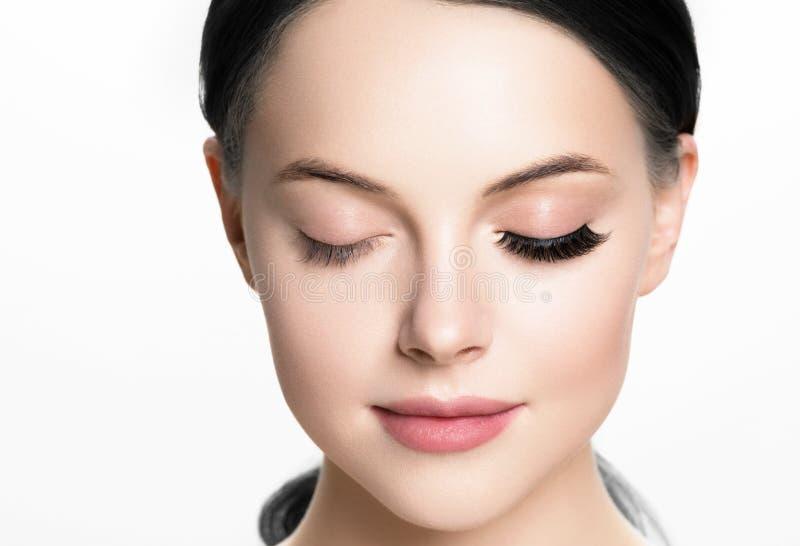 Den härliga kvinnaframsidan med ögonfrans piskar hud för skönhet för förlängningen före och efter sund som naturlig makeup stängd royaltyfria bilder