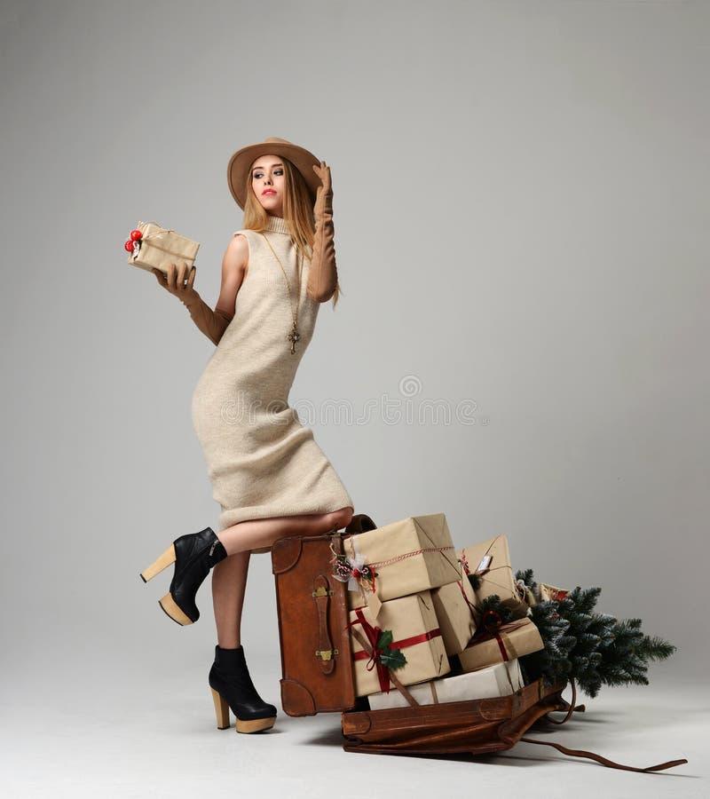 Den härliga kvinnahandelsresanden i hatt med stort öppnar den retro påsen för läder mycket av gåvor för julgåva arkivfoto