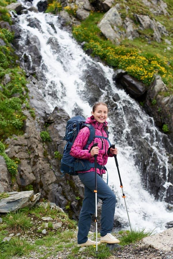 Den härliga kvinnaklättraren som poserar på, vaggar nära den storartade vattenfallet royaltyfri bild