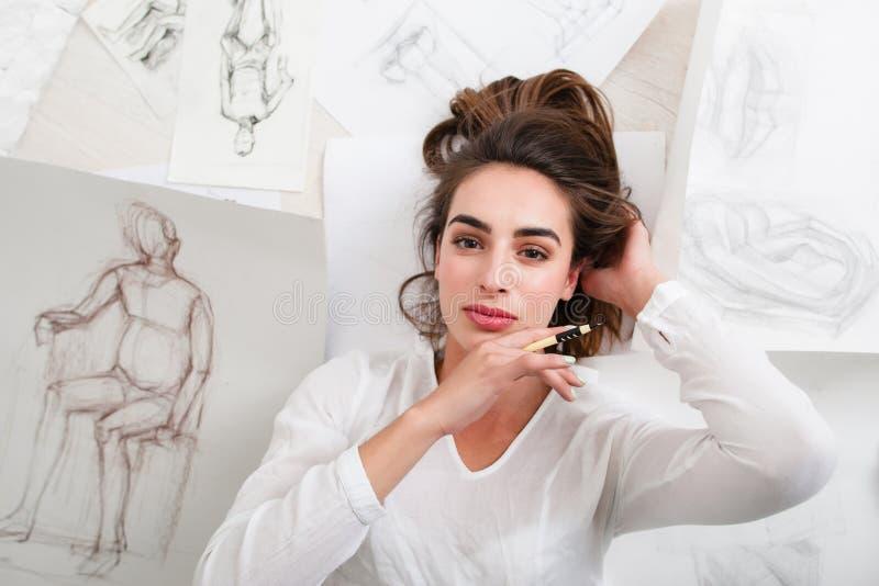 Den härliga kvinnakonstnären som ligger bland, skissar arkivfoto